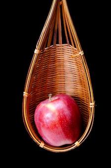 Pommes rouges dans un panier en bois isolé sur fond noir