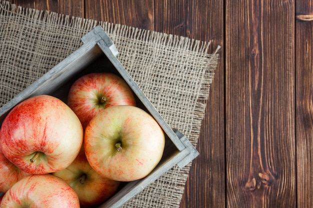 Pommes rouges dans une vue de dessus de boîte en bois sur un sac et un espace de fond en bois pour le texte