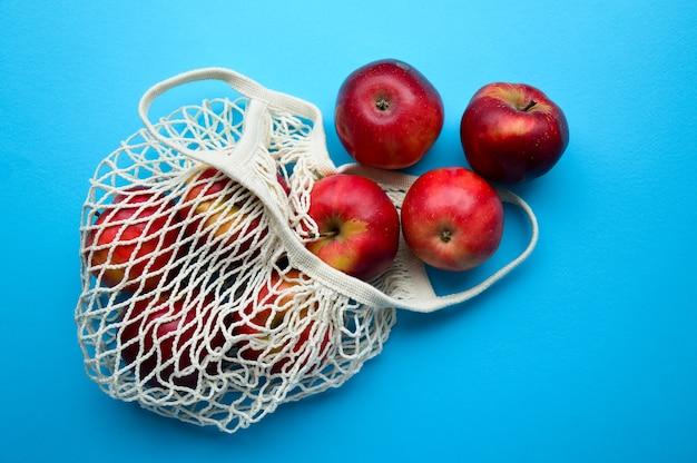 Les pommes rouges débordent du sac d'épicerie sur un fond bleu