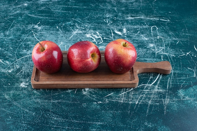 Pommes rouges entières sur planche de bois.