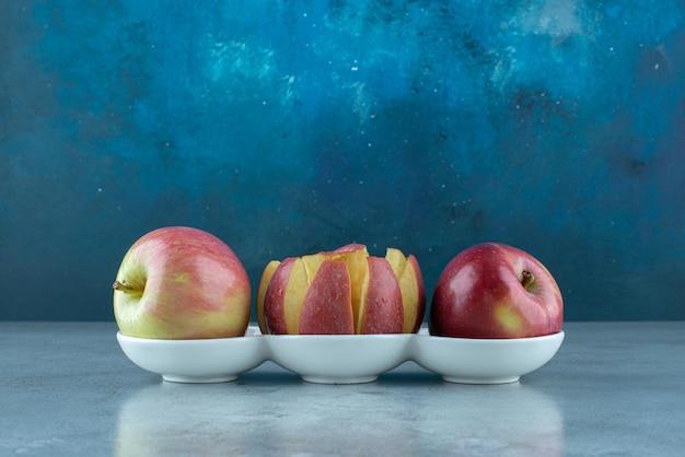 Pommes rouges entières et tranchées dans des tasses blanches.