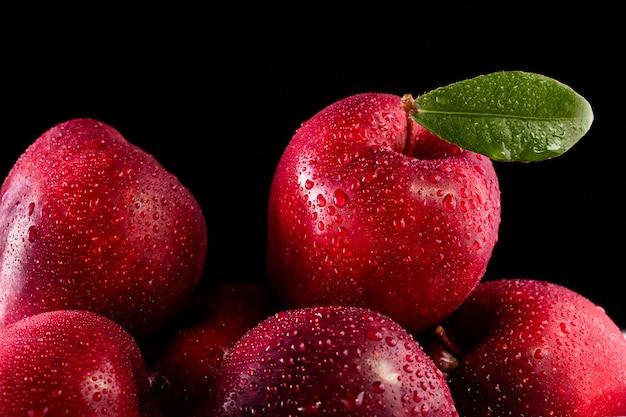 Pommes rouges avec des feuilles sur fond noir