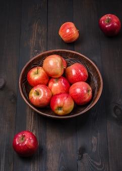 Pommes rouges sur un fond rustique foncé dans un bol en argile. lay plat.