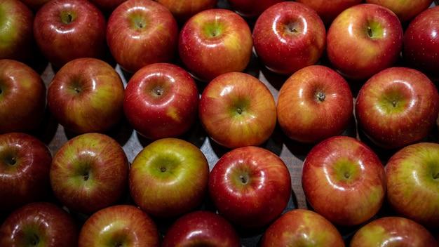 Pommes rouges fraîches sur le comptoir du marché. pommes dans la boîte en carton sur l'étagère de l'épicerie. vue rapprochée des fruits au supermarché. alimentation saine et végétarisme