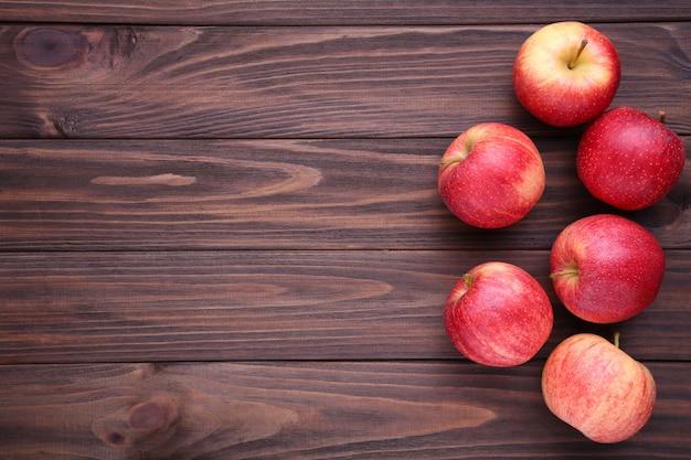 Pommes rouges fraîches sur fond en bois