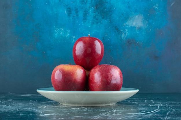 Pommes rouges fraîches sur plaque bleue.