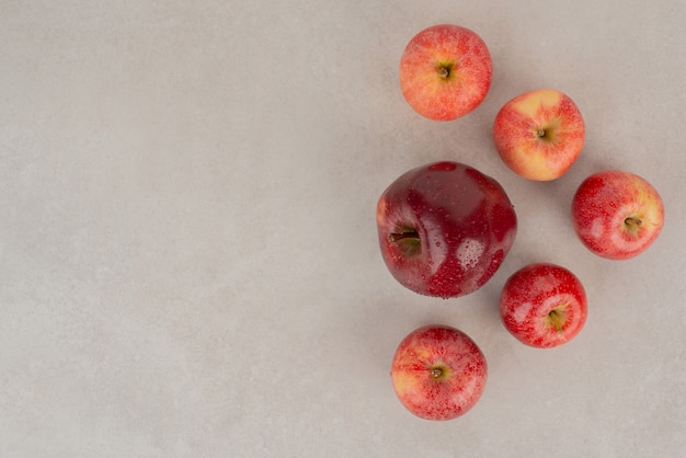 Pommes rouges et fraîches sur tableau blanc.