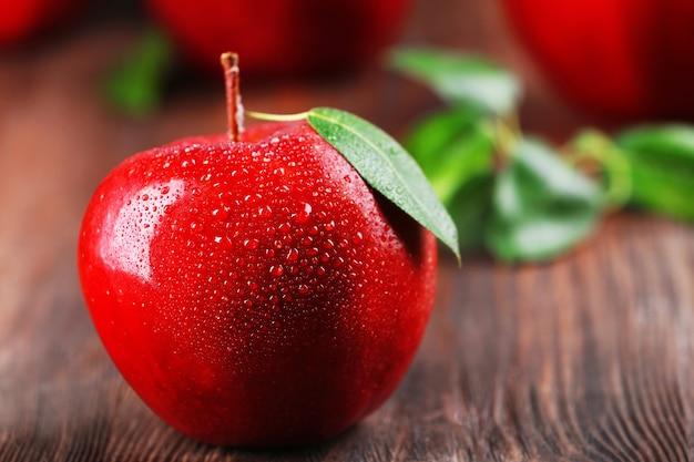 Pommes rouges avec des gouttelettes sur table en bois, gros plan