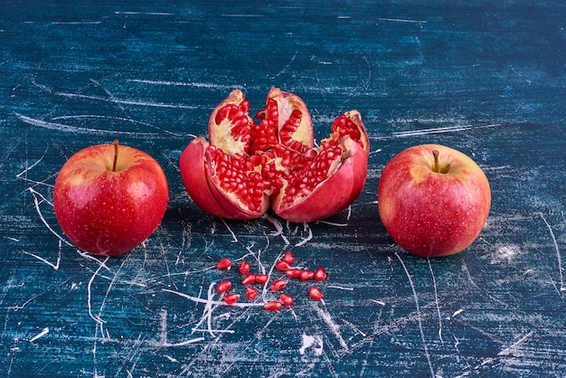 Pommes rouges et grenade sur espace bleu.