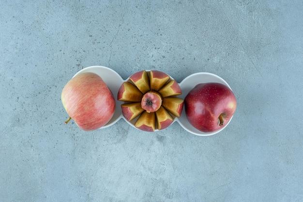 Pommes rouges à l'intérieur de tasses en céramique blanches.