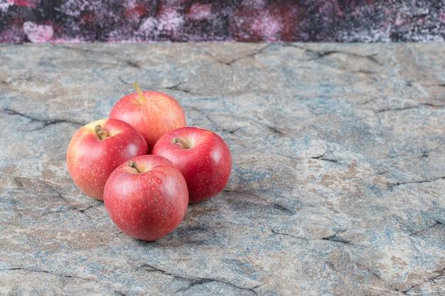 Pommes rouges isolées sur fond de marbre en béton.