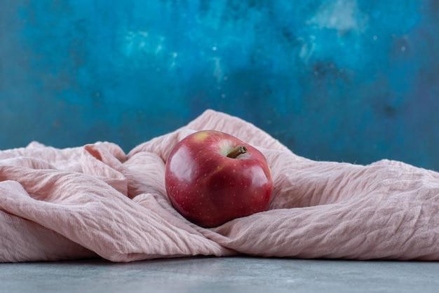 Pommes rouges isolées sur une nappe rose.