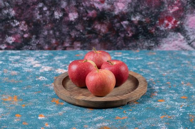 Pommes rouges isolées sur planche de bois.