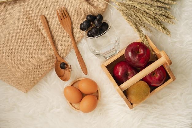 Pommes rouges juteuses fraîches et kiwis dans un panier en bois avec des œufs sur des montagnes russes en bois