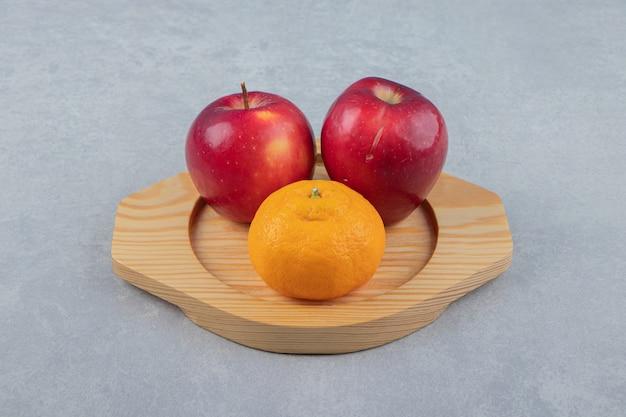 Pommes rouges et mandarine sur plaque de bois