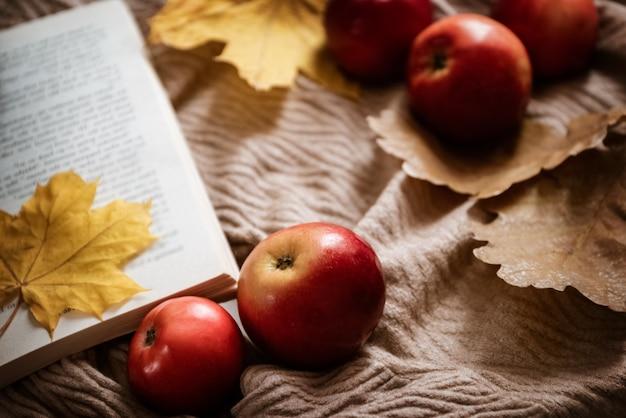 Pommes rouges mûres éparpillées autour d'un livre ouvert avec une feuille d'érable jaune comme signet