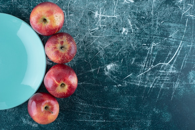 Pommes rouges mûres sur plaque bleue.