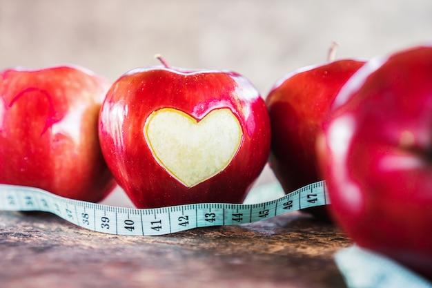 Pommes rouges et ruban à mesurer sur la table
