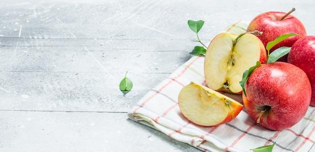 Pommes rouges sur une serviette. sur fond rustique blanc.