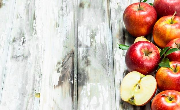 Pommes rouges et tranches de pomme. sur un fond en bois blanc.