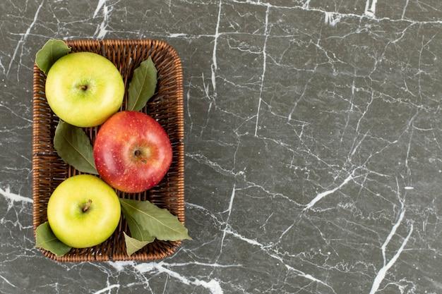 Pommes rouges et vertes biologiques fraîches dans un seau sur fond gris.