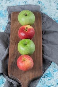 Pommes rouges et vertes isolées sur planche de bois.