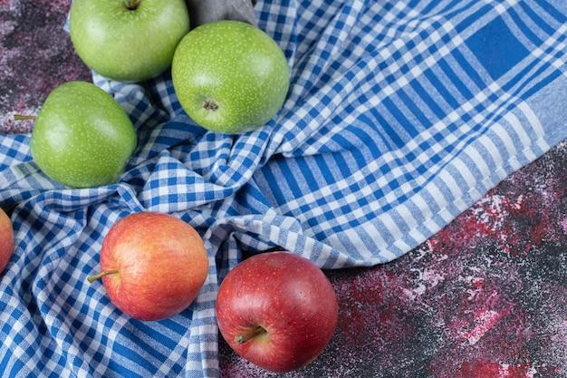 Pommes rouges et vertes isolées sur une serviette à carreaux bleus.