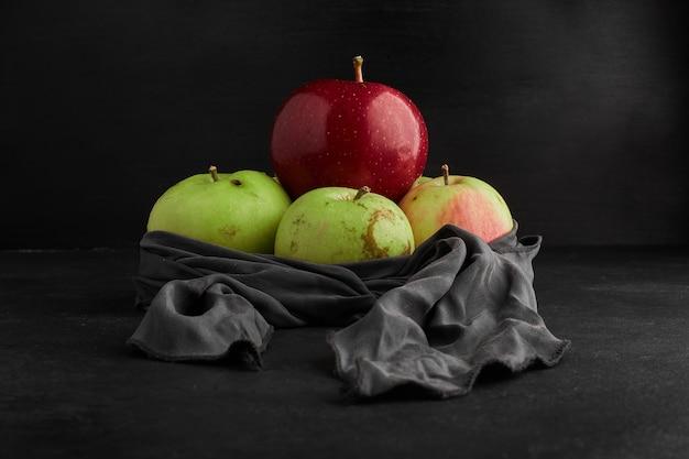 Pommes rouges et vertes sur une nappe grise.