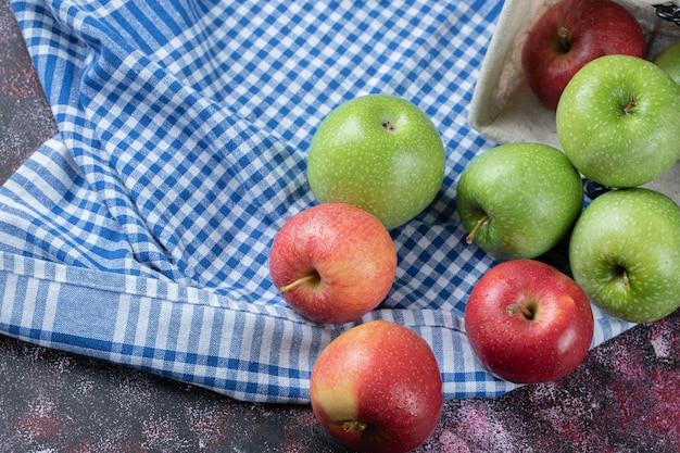 Pommes rouges et vertes sur serviette à carreaux.