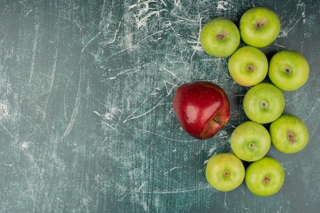 Pommes rouges et vertes sur table en marbre.