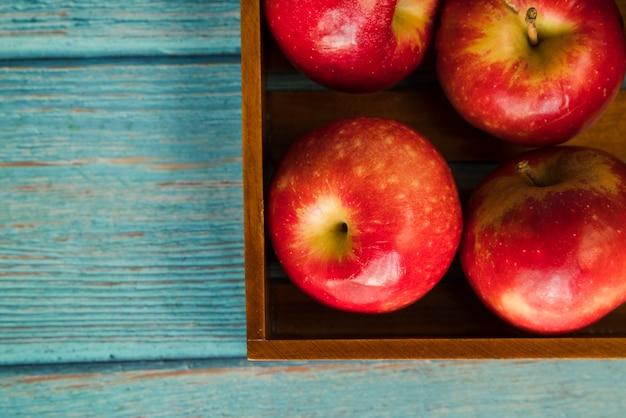 Pommes savoureuses dans une boîte en bois