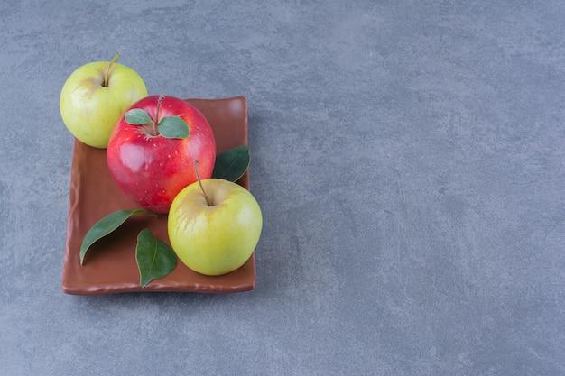 Pommes savoureuses avec des feuilles sur une plaque en bois sur la surface sombre