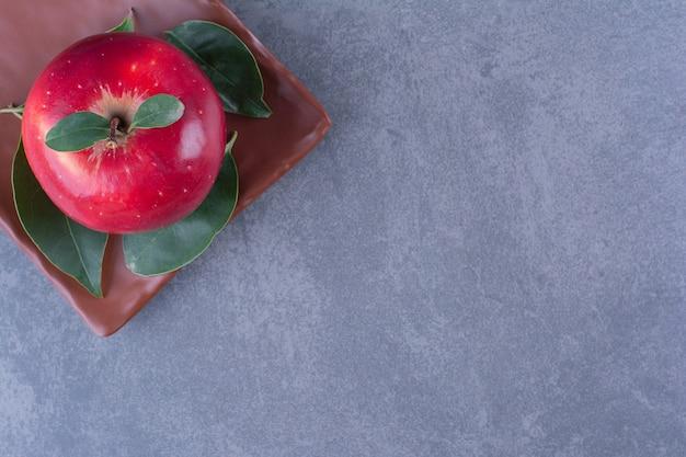 Pommes savoureuses avec des feuilles sur une plaque en bois sur une table en marbre.