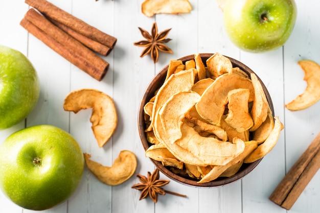 Pommes séchées dans un bol en bois pommes vertes mûres sur la table