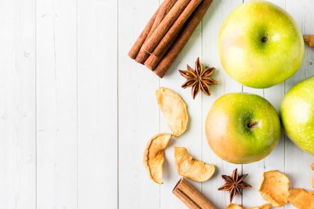 Pommes séchées pommes vertes mûres, bâtons de cannelle anis étoilé sur la table espace copie