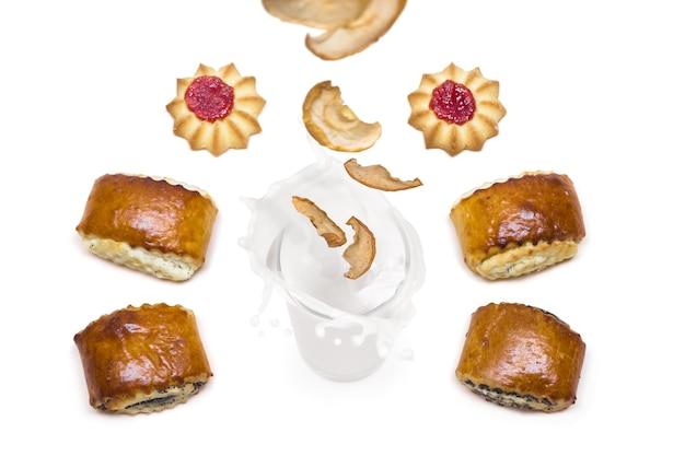 Pommes séchées tombant dans un verre de lait avec des éclaboussures autour desquelles sont de délicieux biscuits