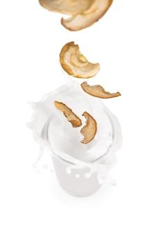 Pommes séchées tombant dans un verre de lait avec des éclaboussures
