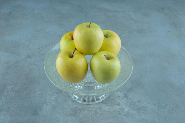 Pommes sur un socle en verre, sur la table en marbre.