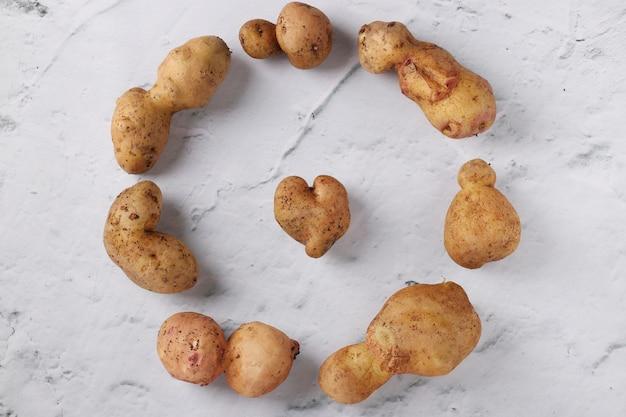 Pommes de terre anormales biologiques laides sur fond de marbre, légumes biologiques concept, vue de dessus