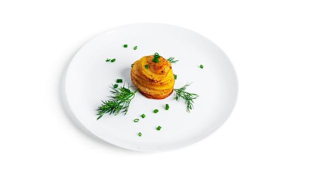 Pommes de terre au four aux herbes sur plaque blanche isolée sur blanc.