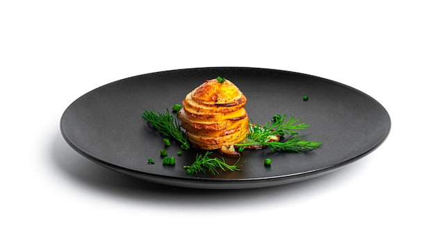 Pommes de terre au four aux herbes sur plaque noire isolée sur blanc.