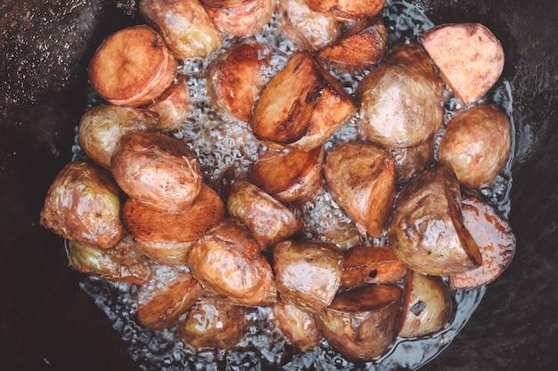 Pommes de terre au four cuites dans un chaudron de jardin avec du bois de chauffage, avec beaucoup d'huile de tournesol bouillante