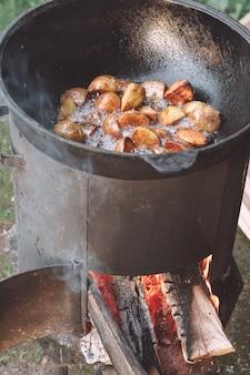 Pommes de terre au four cuites dans un chaudron de jardin avec du bois de chauffage brûlant dedans, avec beaucoup d'huile de tournesol bouillante. verticale