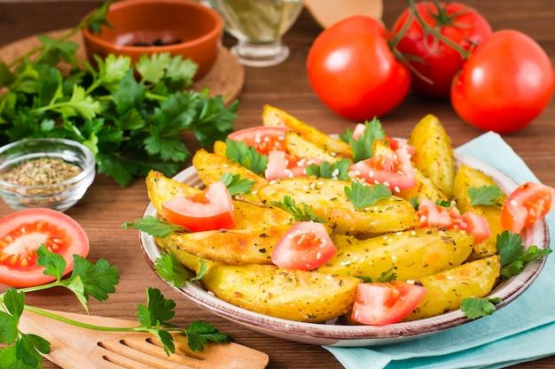 Pommes de terre au four dans une pelure avec des tomates dans une assiette, légumes, herbes et épices sur une table en bois