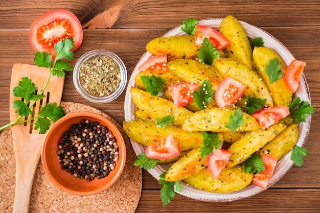 Pommes de terre au four dans une pelure avec tomates, herbes, épices et sésame dans une assiette, vue de dessus