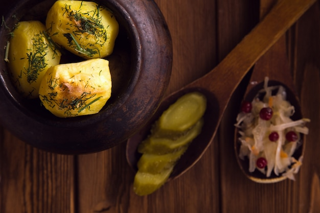 Pommes de terre au four dans un vieux pot sur une surface en bois avec chou mariné et concombre