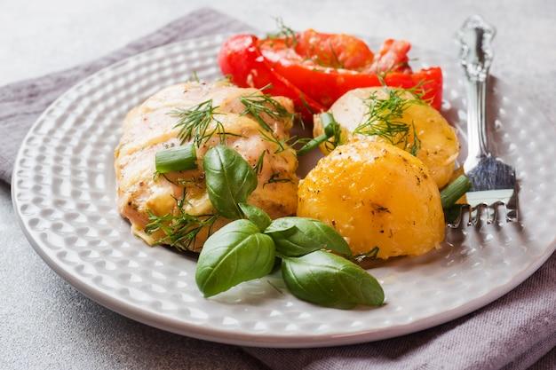 Pommes de terre au four avec du poulet et des légumes sur une assiette