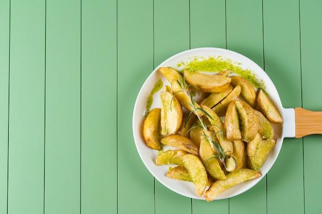 Pommes de terre au four avec sauce verte et romarin sur une plaque blanche sous la forme d'une poêle. pommes de terre frites avec sauce pesto sur une table verte.
