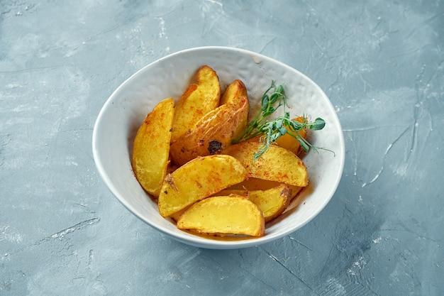 Pommes de terre au four selyansky aux épices dans un bol blanc. quartiers de pommes de terre au four