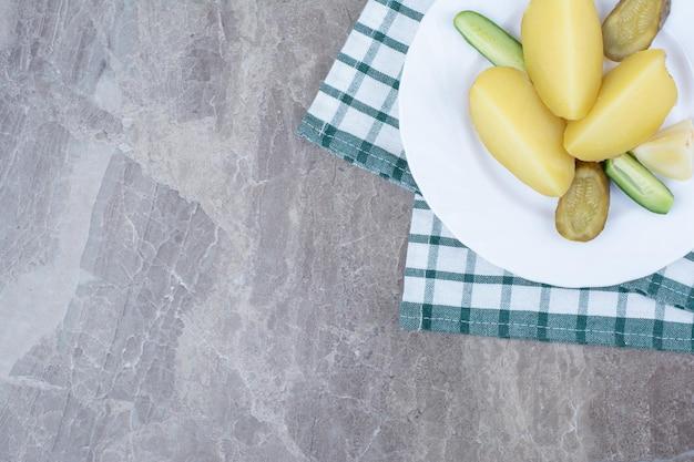 Pommes de terre bouillies et divers légumes sur plaque blanche.
